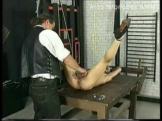 Hot slave with lying on table gets metal clamps removed from pussy and hot candle wax over her body