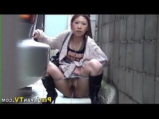 Pissing japanese babe squats behind car